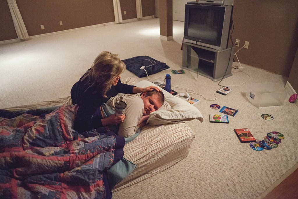image of a woman comforting a young man on a mattress on the floor