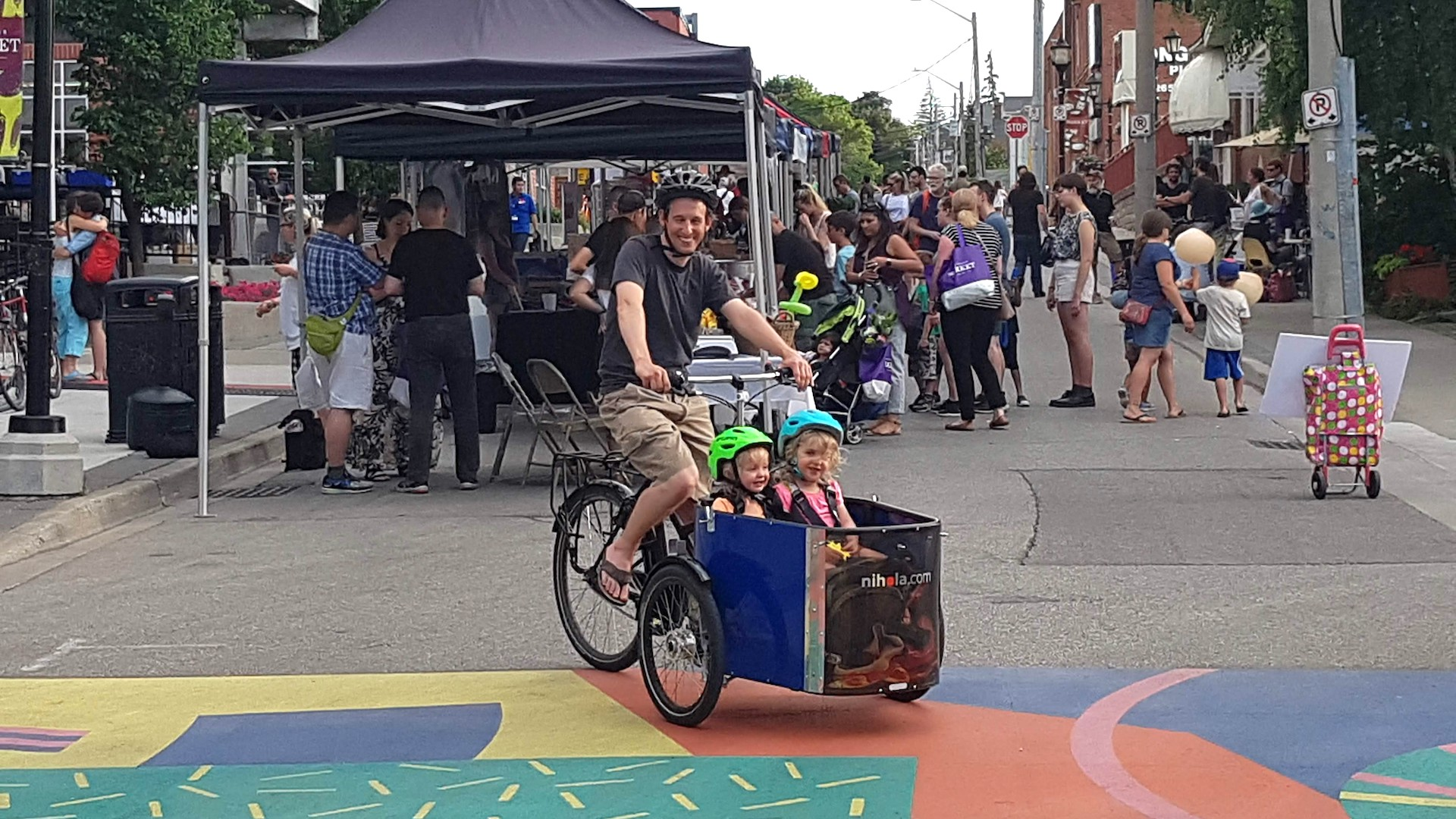Darren on his cargo bike with two children, on a street filled with pedestrians.