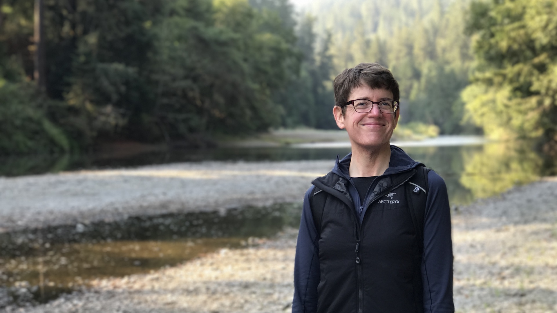 Kim Goodwin is standing beside a river wth trees in the background