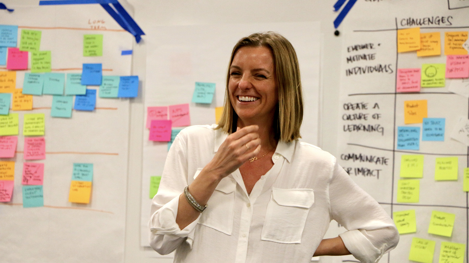 A smiling Teresa Brazen stands in front of a whiteboard covered with sticky notes and writing