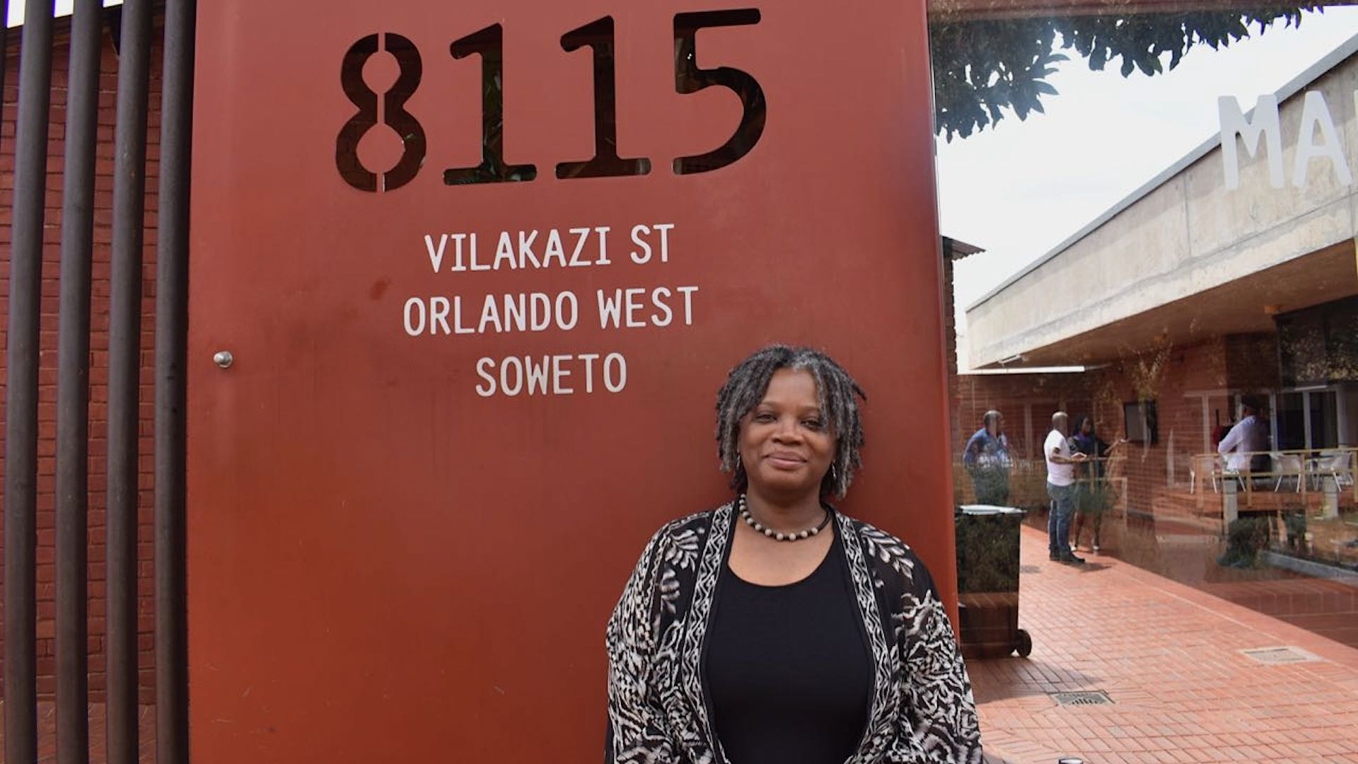 Lisa Welchman stnding in front of a red wall in Soweto