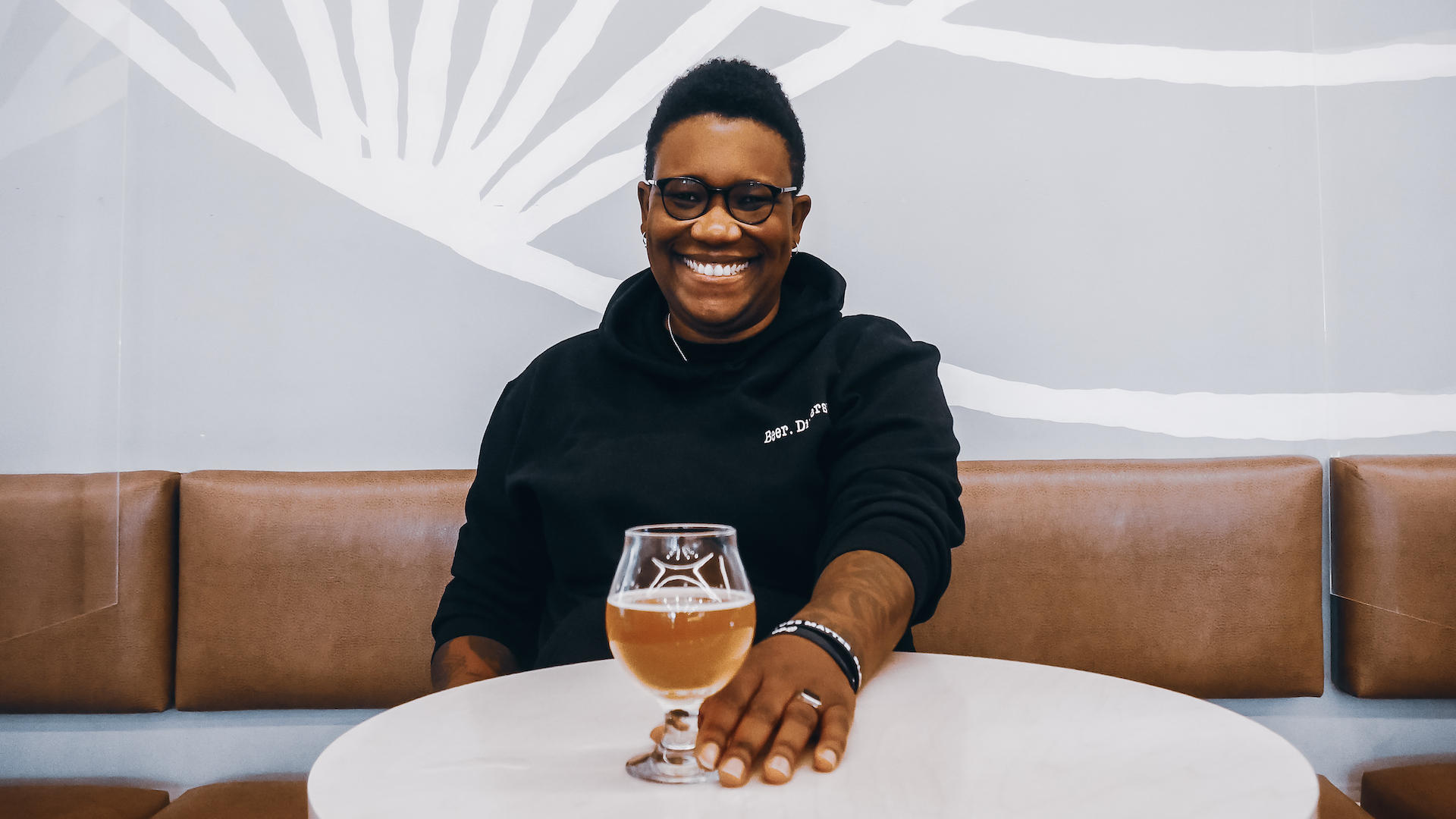 Ren Navarro sitting at a table with a glass of beer